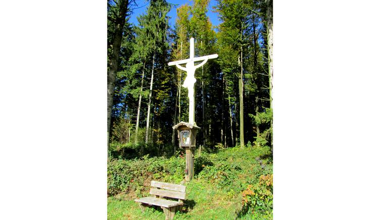 Blick auf das Holzkreuz, davor ein Holzbankerl, im Hintergrund ein Wald