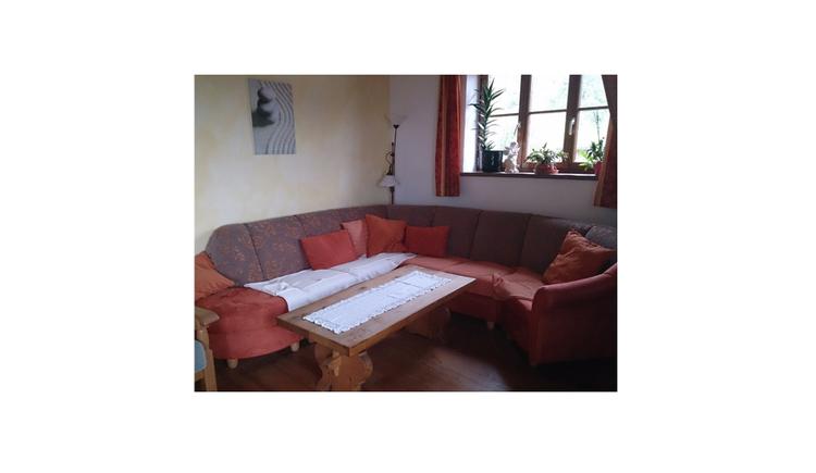 Wohnraum mit Couch mit Tisch, im Hintergrund ein Fenster