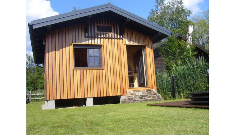 Blick auf das kleine Holzhaus umgeben von Wiesen.