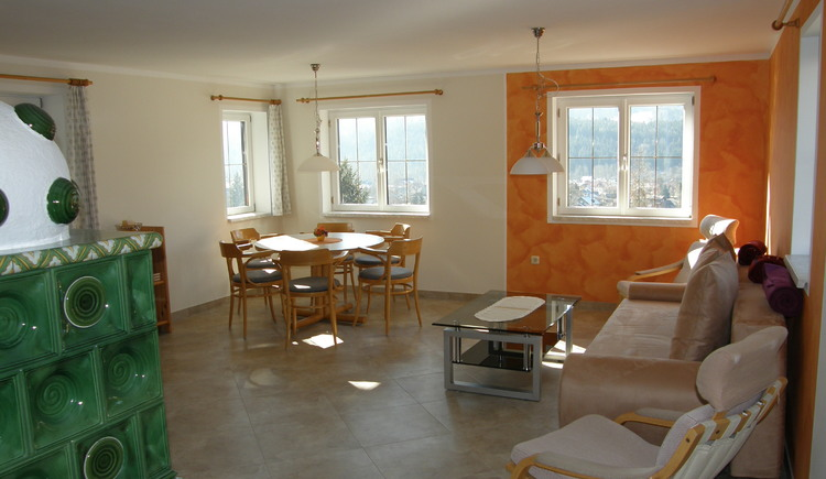 The spacious living area with dining area, living area and tiled stove invites you to linger