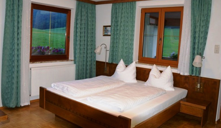bedroom with double bed, bedside table with lamps\n