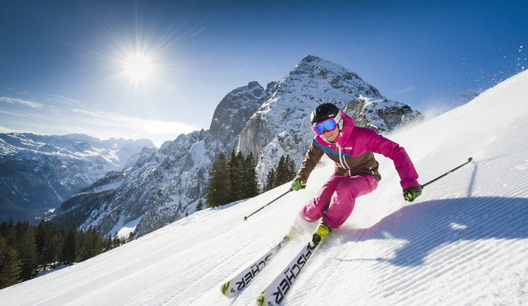 Eine Skifahrerin fetzt die Piste hinunter. Im Hintergrund befindet sich der imposante Dachstein. (© OÖ Tourismus/Erber)