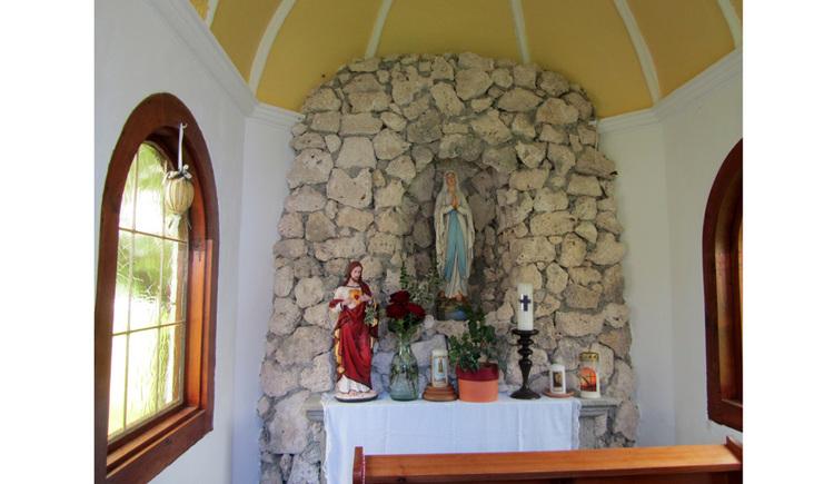 Blick auf den Altar mit Heiligenfigur, Kerzen, Blumen, im Hintergrund eine Steinwand seitlich ein Fenster