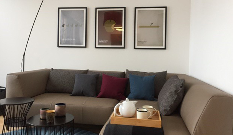Living room with sofa, small table, tray with pot and cups and pictures on the wall.