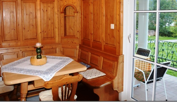 Eßbereich mit Eckbank Tisch und Stühle, seitlich Balkontür mit Blick auf die Terrasse wo sich ein Tisch und Stühle befinden