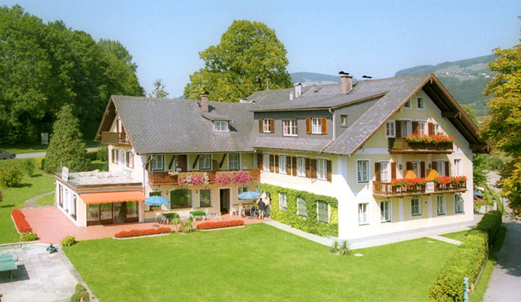 Blick auf das Hotel, im Vordergrund ein großer Garten, im Hintergrund Bäume