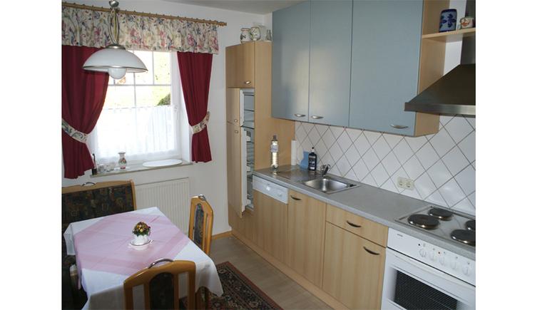 Küche mit Herd, Kühlschrank, seitlich Tisch und Stühle, im Hintergrund ein Fenster