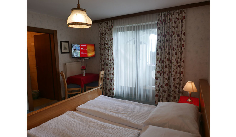 Schlafzimmer mit Doppelbett, Nachtkästchen mit Tischlampe, im Hintergrund eine Balkontüre, Tisch mit Stühlen, darüber ein Fernseher, offene Tür ins Badezimmer