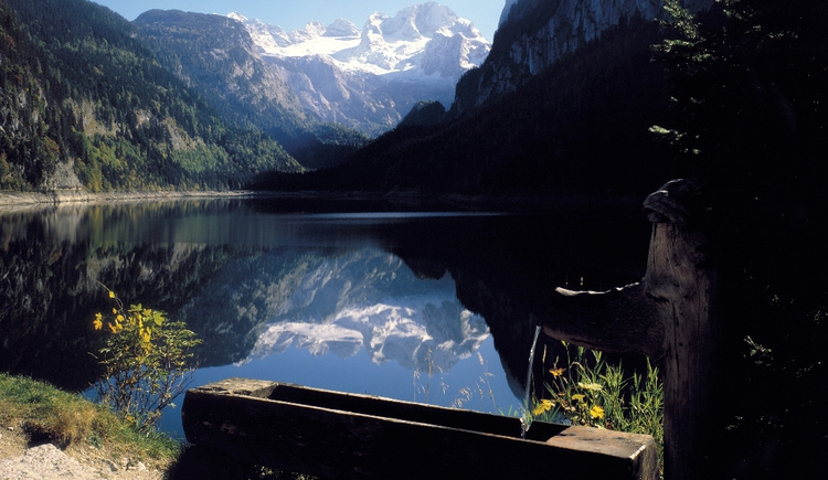 The lake with a fountain and the mountain Dachstein. The typical photo scene where the mountain is reflected in the lake.