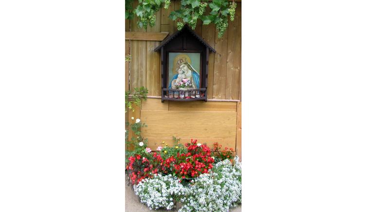 Blick auf ein Heiligenbild, darunter Blumen