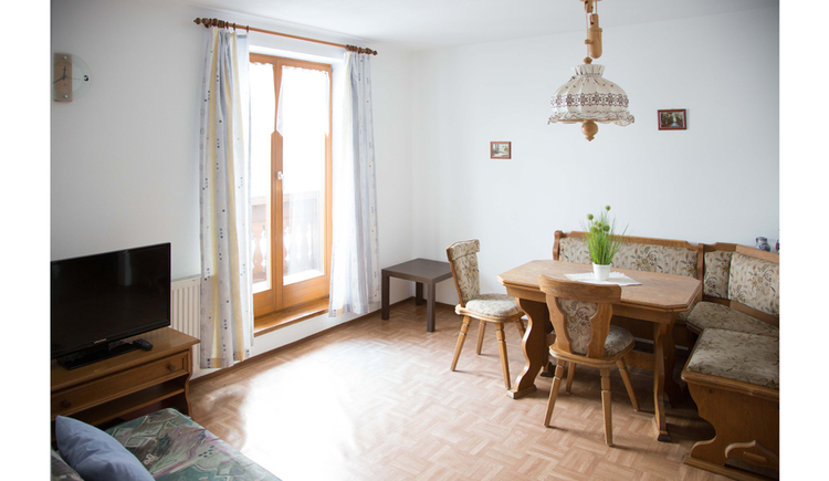 Wohnbereich mit Küche, Tisch und Eckbank, seitlich ein Fernseher und eine Balkontür