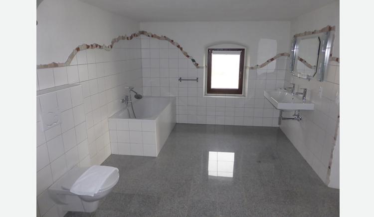 Badezimmer mit Badewanne, Waschbecken, Toilette, im Hintergrund ein Fenster
