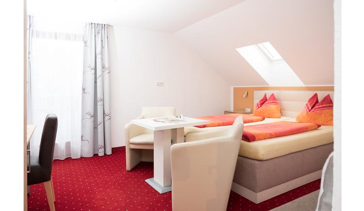 Schlafzimmer mit Doppelbett seitlich, davor ein Tisch mit Sesseln, im Hintergrund eine Balkontür