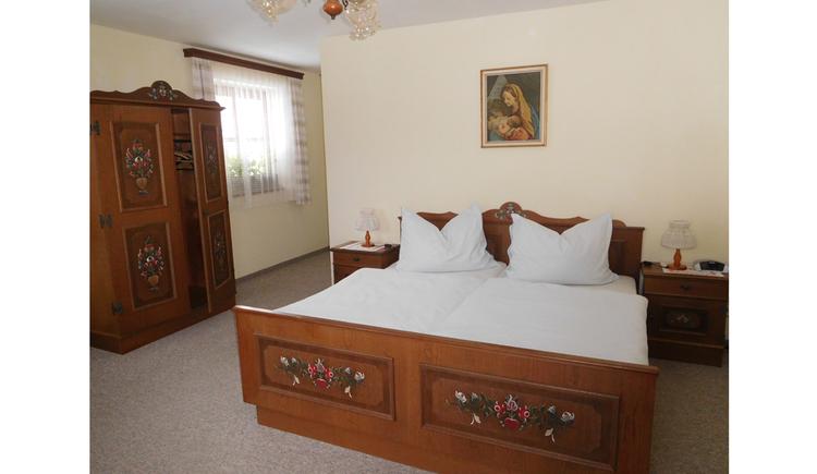 Schlafzimmer mit Doppelbett, seitlich ein Kleiderschrank, Fenster