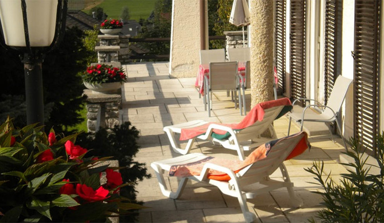 Terrace with deckchairs, chairs, flowers