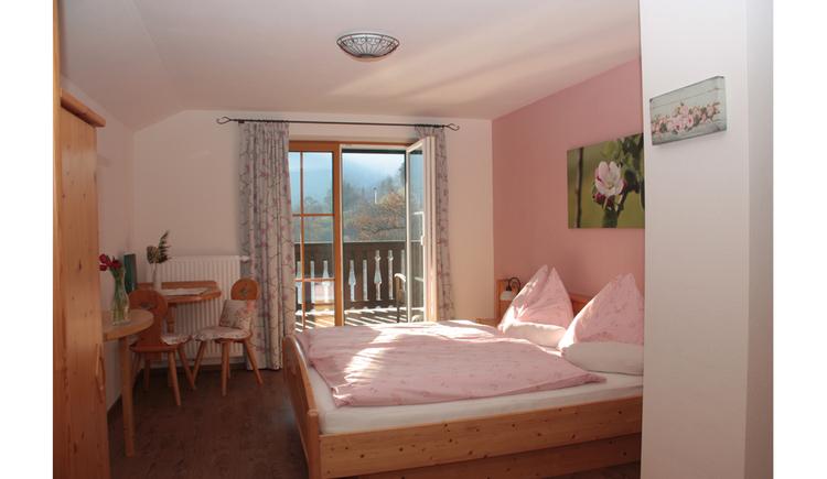 Doppelbett, seitlich ein Kleiderschrank, Tisch und Stühle, im Hintergrund Blick auf die offene Balkontür ins Freie