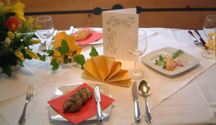 gedeckter Tisch mit Blumen, Karte, Gebäck und verschiedenen Aufstrichen. (© www.mondsee.at)