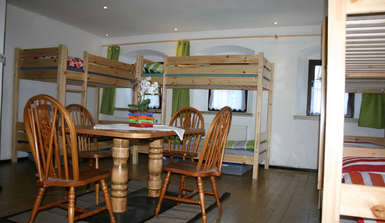 Sleeping room with wooden stockbeeds, in front view you will see a table with flowers and chairs.