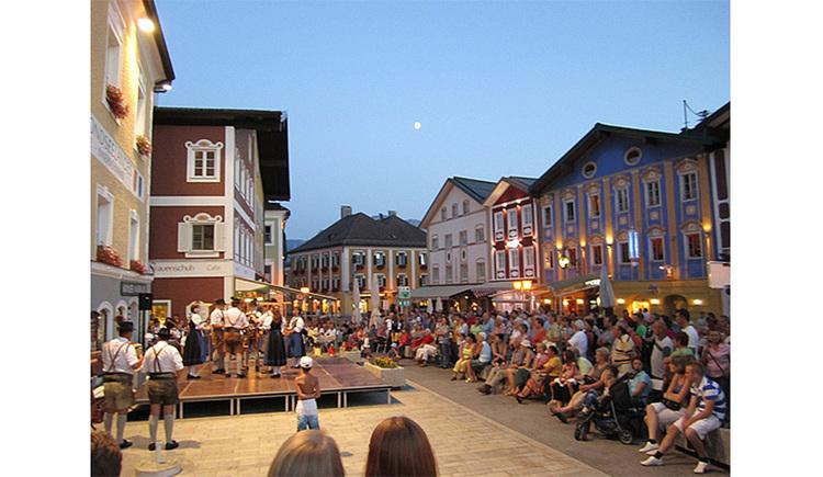 Tanzgruppe auf der Bühne, seitlich viele Zuschauer, Häuser. (© Tourismusverband MondSeeLand)