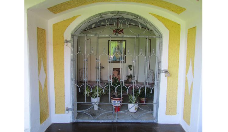 Blick auf die Kapelle mit Gitter, dahinter, Blumen, Heiligenbild, Kreuz