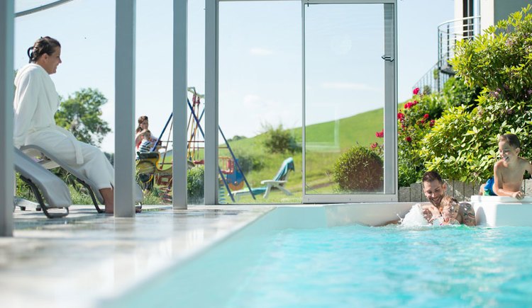 Swimming pool with a family in the water, in the background outside swing with deck chair