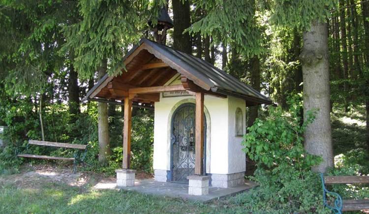 eine kleine Kapelle am Waldrand, daneben eine Bank zum hinsetzen. (© www.mondsee.at)