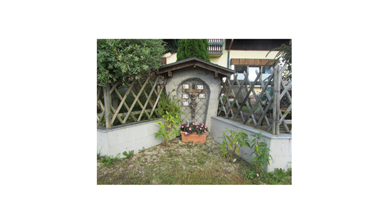Blick auf das Marterl mit einem Kreuz, seitlich eine Mauer mit Holzzaun