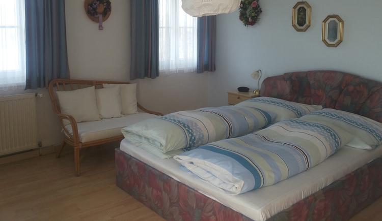 Schlafzimmer mit Doppelbett, kleine Sitzgelegenheit zwischen den Fenstern