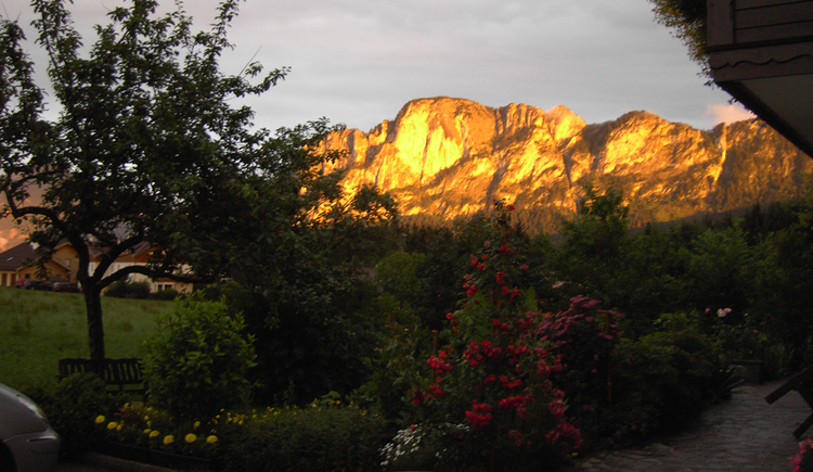 View in front of the house on the flowers and shrubs, in the background evening mood on the mountains at sunset