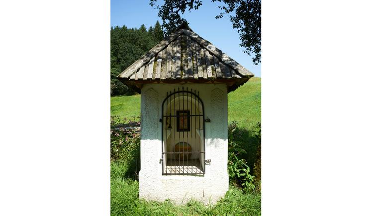 Blick auf die Kapelle, hinter Gitter befindet sich ein Gemälde, im Hintergrund Wiesen und Bäume