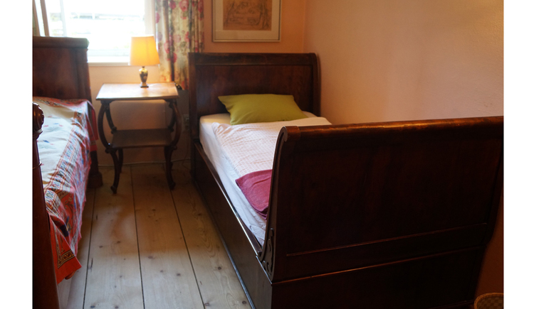 Zimmer mit Einzelbetten, kleiner Beistelltisch mit Tischlampe, im Hintergrund ein Fenster