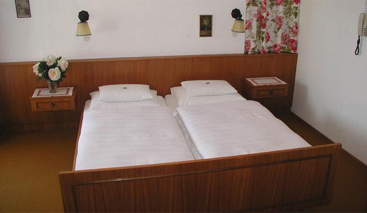 Schlafzimmer mit Doppelbett, Nachtkästchen, Lampen an der Wand