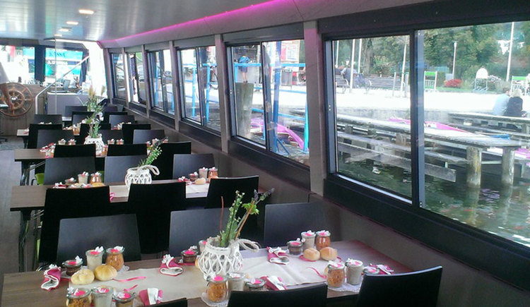 Interior of the ship with some tables and chairs. On the tables there are some snacks and flowers.