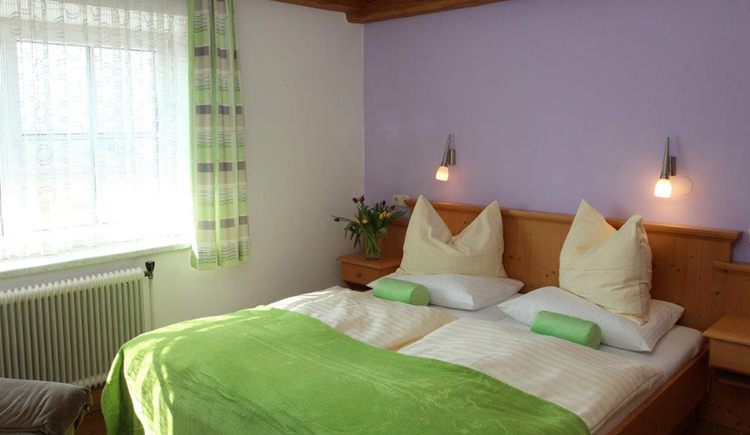 Schlafzimmer mit Doppelbett, seitlich ein großes Fenster