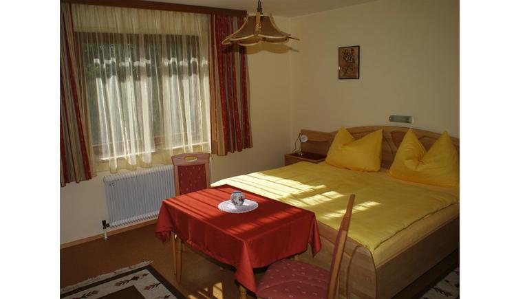 Schlafzimmer mit Doppelbett, davor ein Tisch und Stühle, seitlich ein Fenster