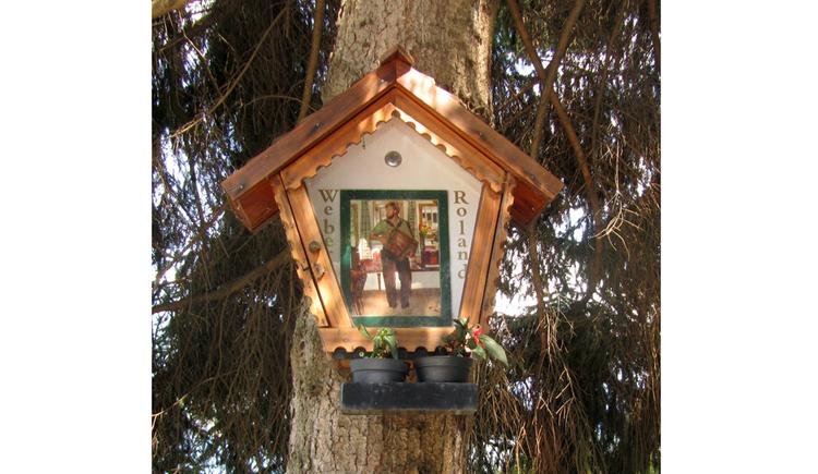 Blick auf ein Holzmarterl auf einem Baum