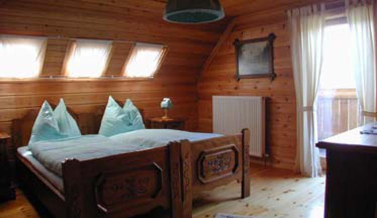 Rustikal eingerichtetes Schlafzimmer mit Doppelbett und Balkon. (© Rehn)