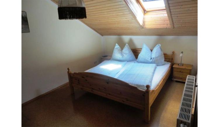 Schlafzimmer mit Doppelbett, Nachtkästchen, Tischlampe, seitlich ein Heizkörper, Dachfenster