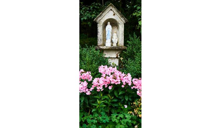 Blick auf den Bildstock, im Vordergrund Blumen