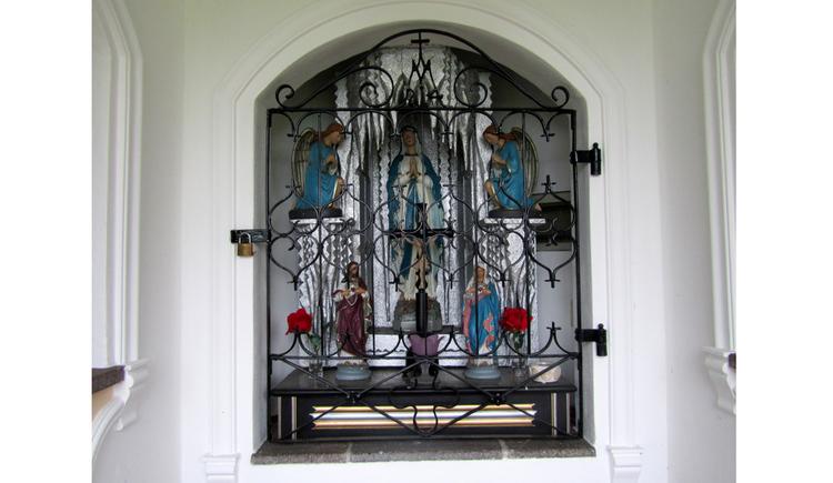 hinter Gitter befinden sich Heiligenfiguren, Blumen