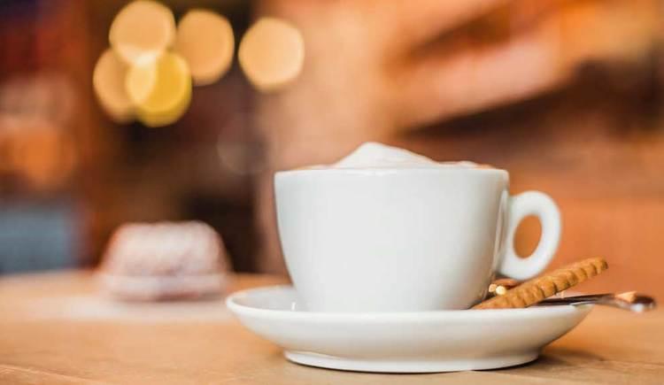 Cappuccino beim Obauer, im Hintergrund ein mit Zucker bestreuter Gugelhupf. (© Obauer)