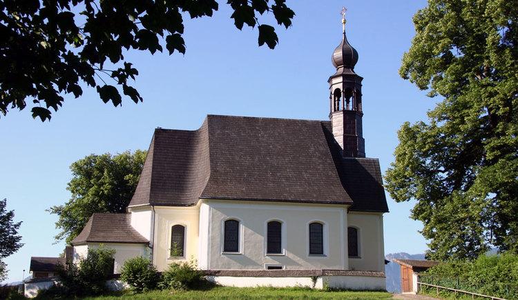 Außenansicht der Kirche mit Bäumen auf der Seite. (© www.mondsee.at)