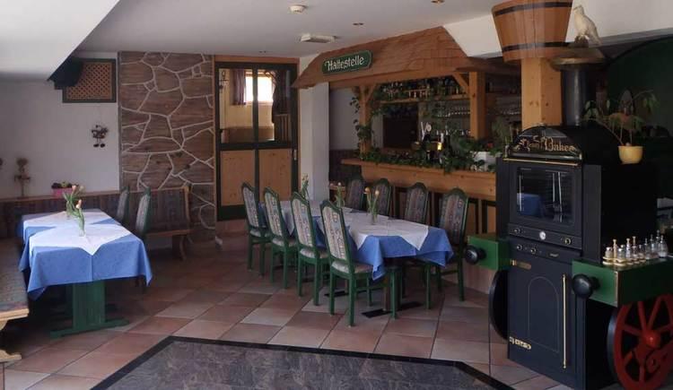 Innenbereich mit Tischen und Stühlen und einer Lokomotive