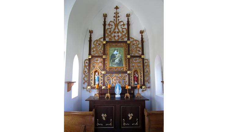 Blick auf einen Altar, mit Heiligenfigur, Heiligenbild, seitlich Bänke