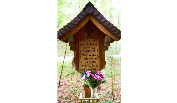 Blick auf ein Holzmarterl, im Vordergrund eine Vase mit Blumen, im Hintergrund ein Wald