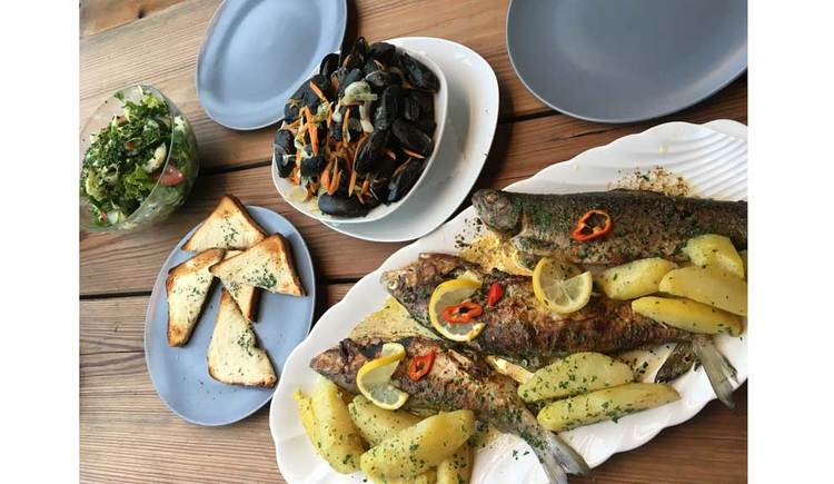 Fischplatte mit Kartoffeln, Muscheln, Salat und Toastbrot