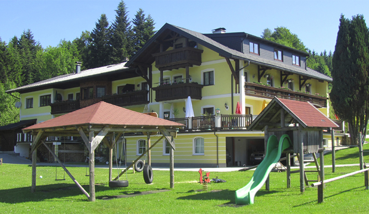 In the foreground a playground, with slide, swings, in the background the house