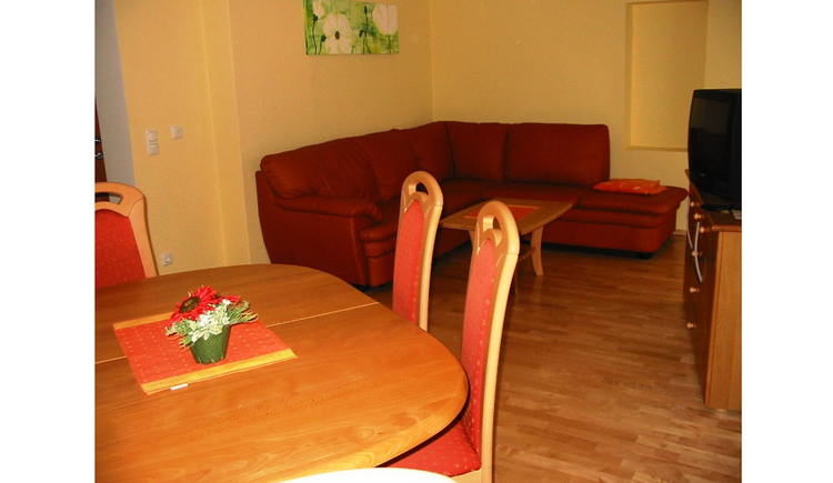 Dining area with table and chairs, in the background sofa, table, opposite a chest of drawers with TV