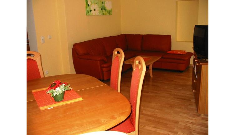 Essbereich mit Tisch und Stühle, im Hintergrund Sofa, Tisch, gegenüber eine Kommode mit Fernseher