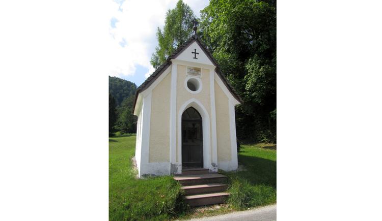 Blick auf die Kapelle in einer Wiese, im Hintergrund ein Wald